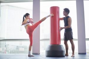 サンドバックでキックボクシングトレーニングしている女性